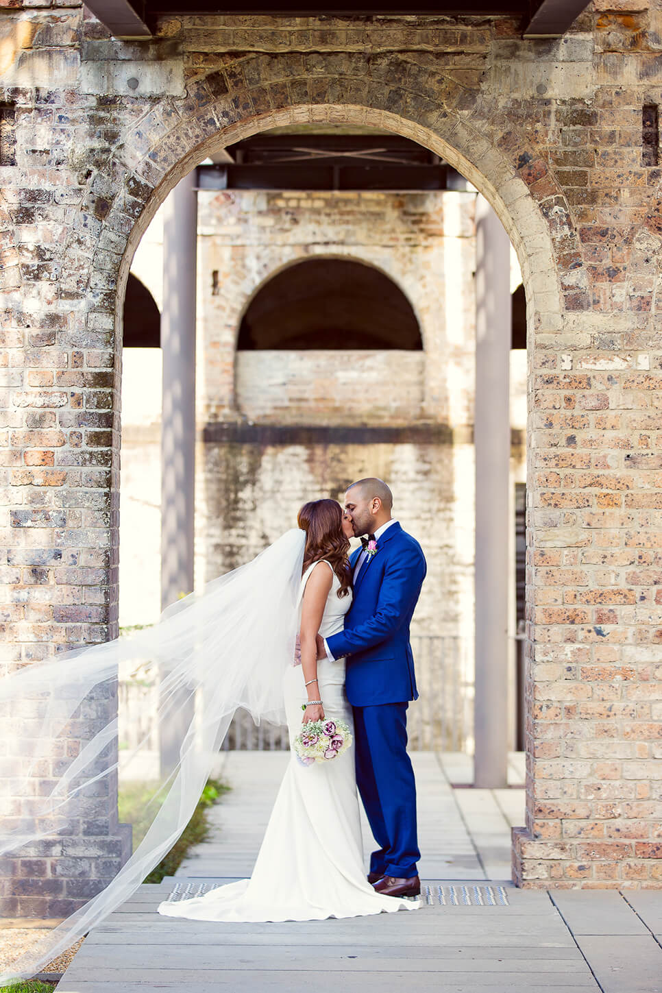 bride and groom kissing under archway