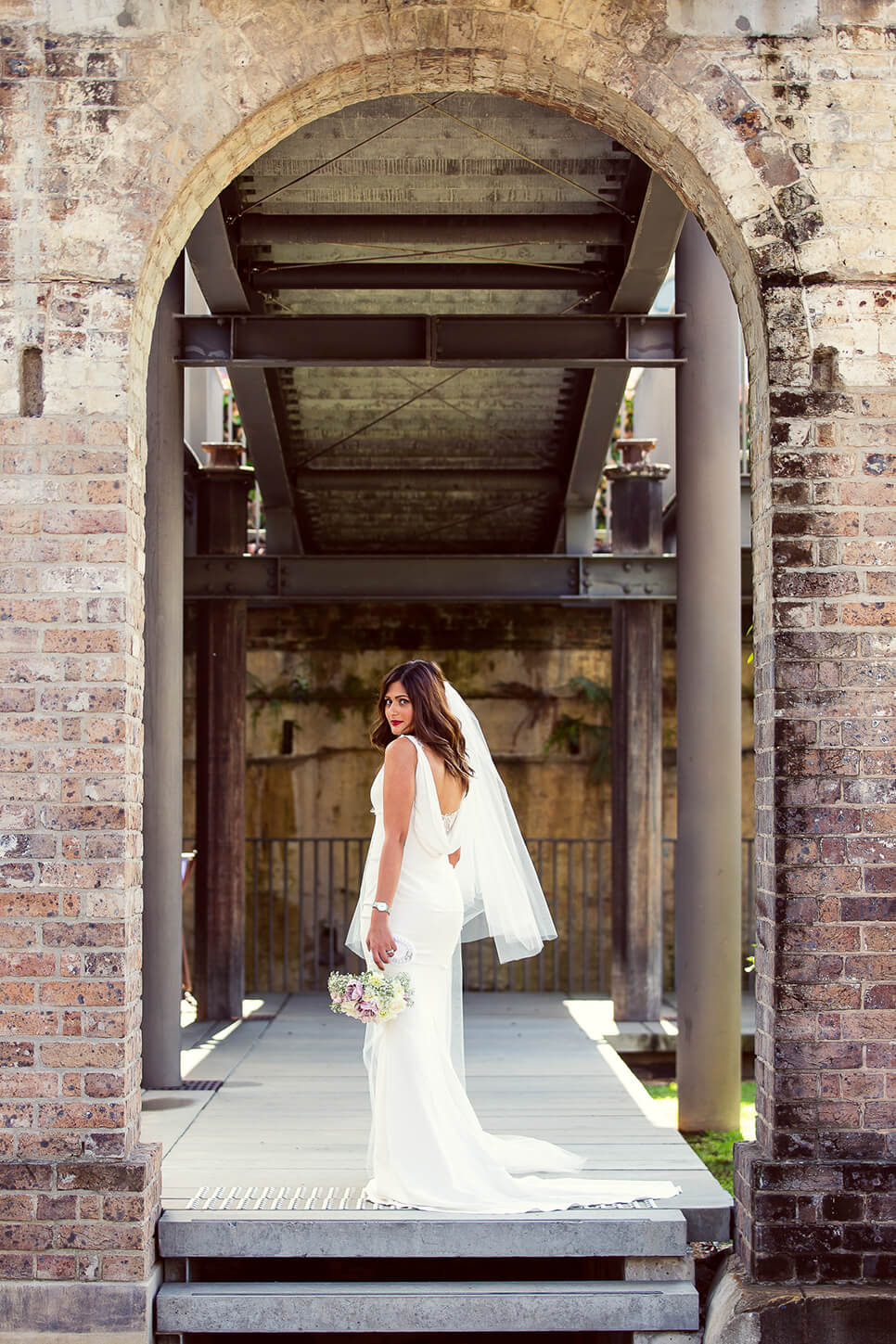 Bride looking back under archway holding flowers