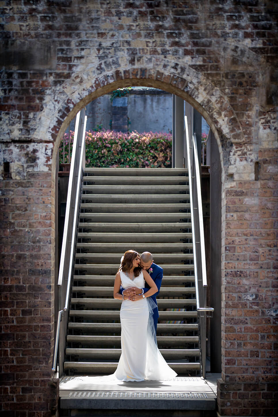 groom with hands around bride's waist at bottom of staircase