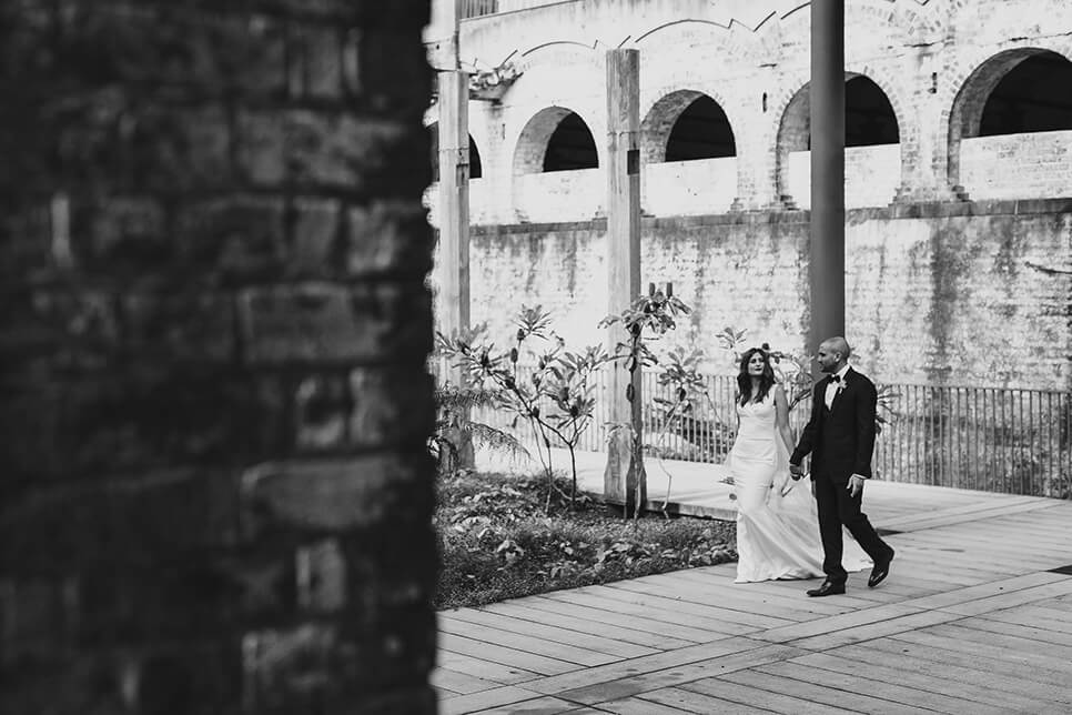 Bride and Groom walking down path holding hands