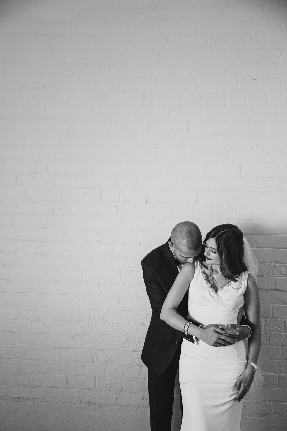 Bride and Groom hugging in front of white painted brick wall
