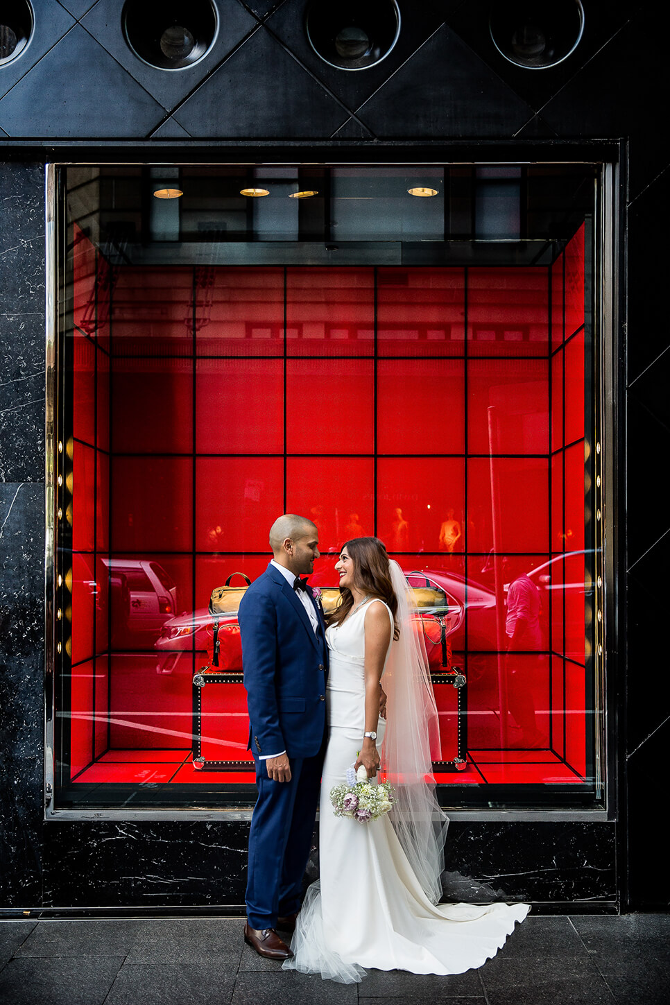Bride and Groom in front of store window with a red background