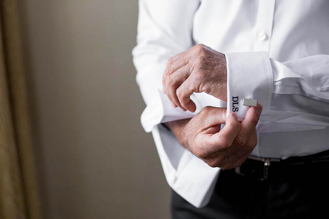 groom doing up cufflinks