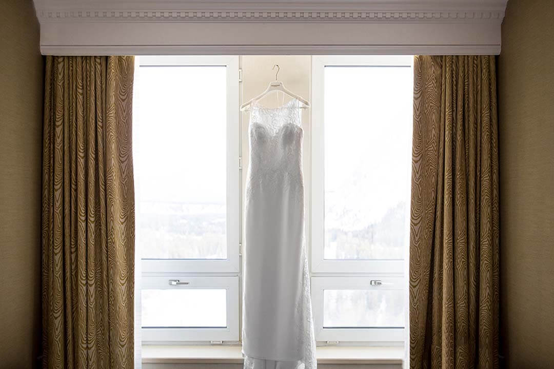 wedding dress hanging up in front of window overlooking snow