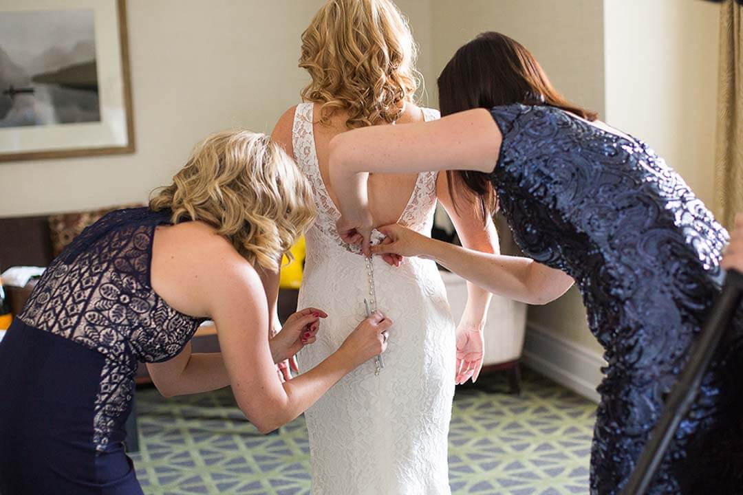 doing buttons up on bride's dress